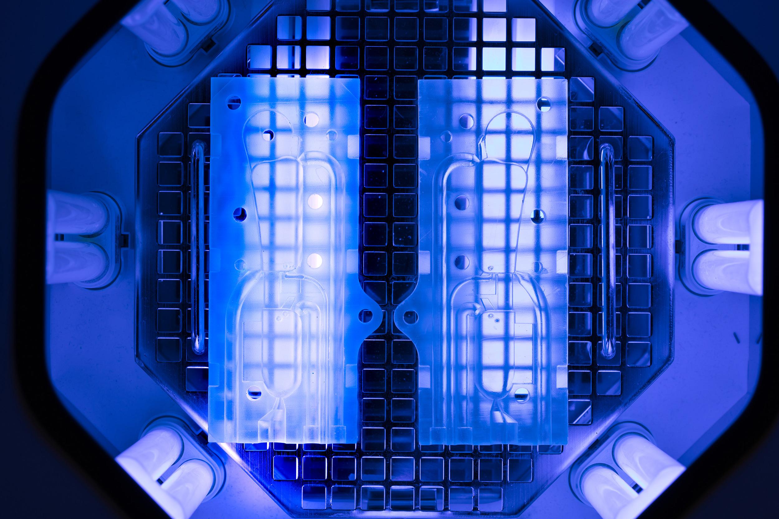 Post-traitement de pièces imprimées en 3D dans une chambre à UV.