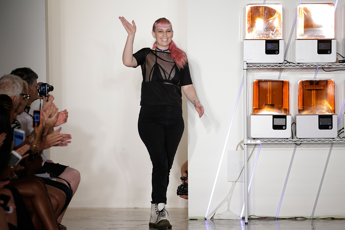 Chromat designer Becca McCharen-Tran walks out on the runway at her New York Fashion Week show, with a backdrop of 3D printers.