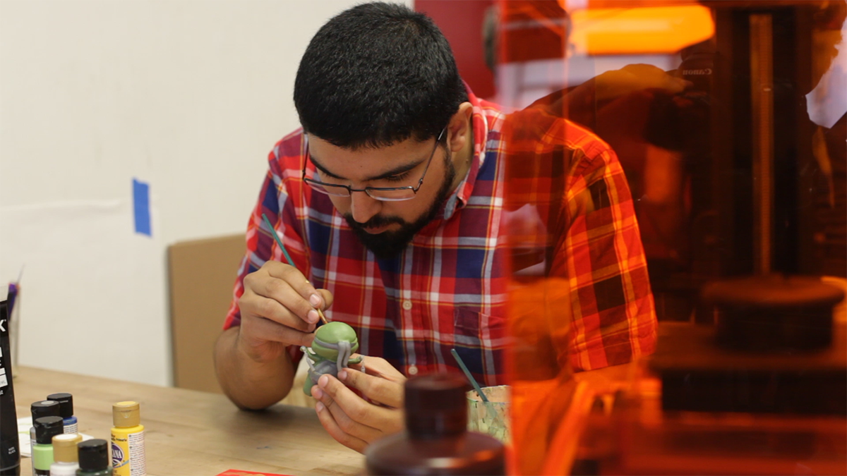 A man sits at a desk next to a Form 1+ 3D printer painting models