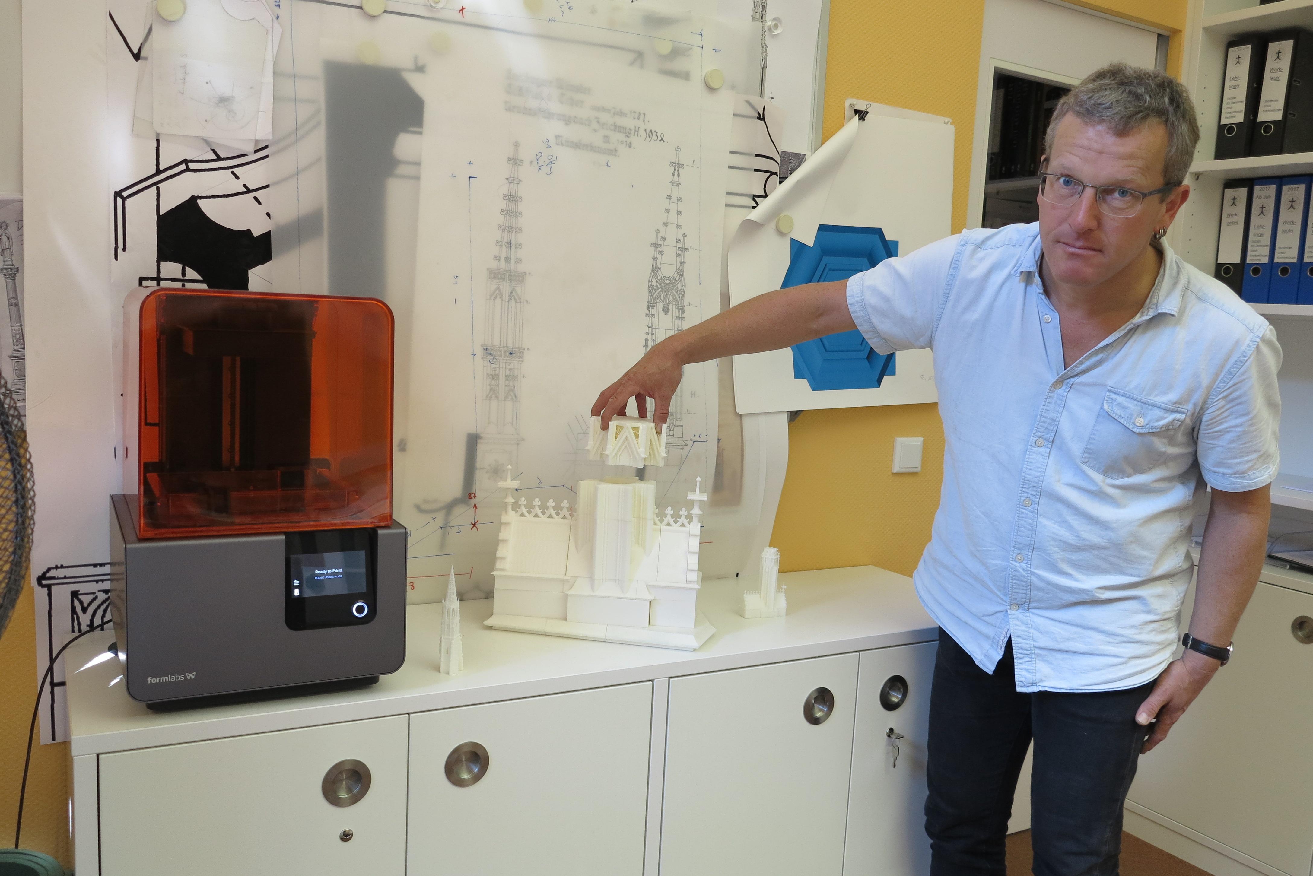 Uwe Zäh mit seinem Form 2 3D-Drucker und Teilen des Chor-Restaurationsprojekt mit Bauzeichnungen im Hintergrund.