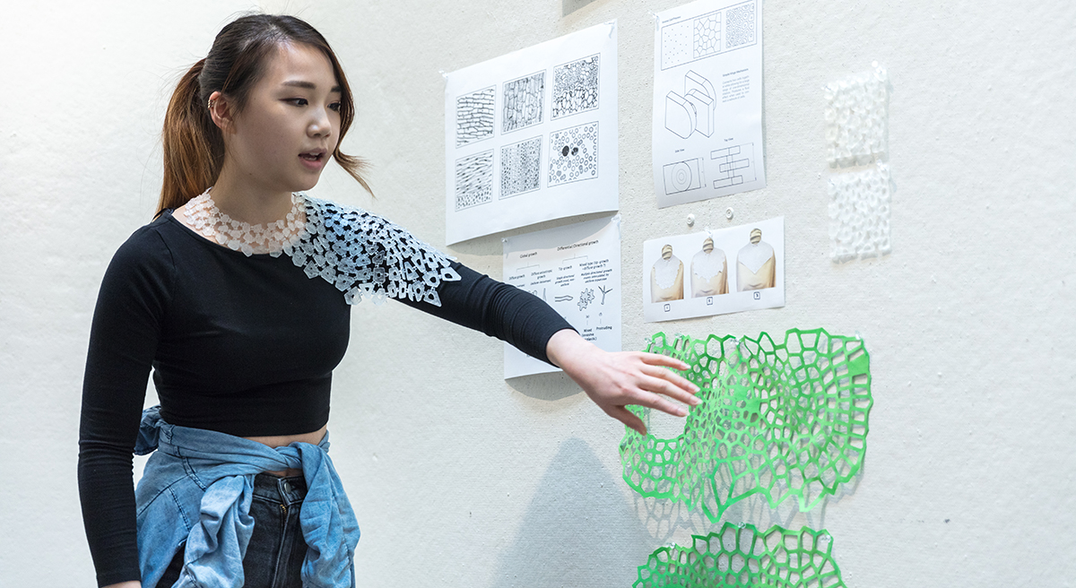 A college student presents 3D printed and laser cut designs.