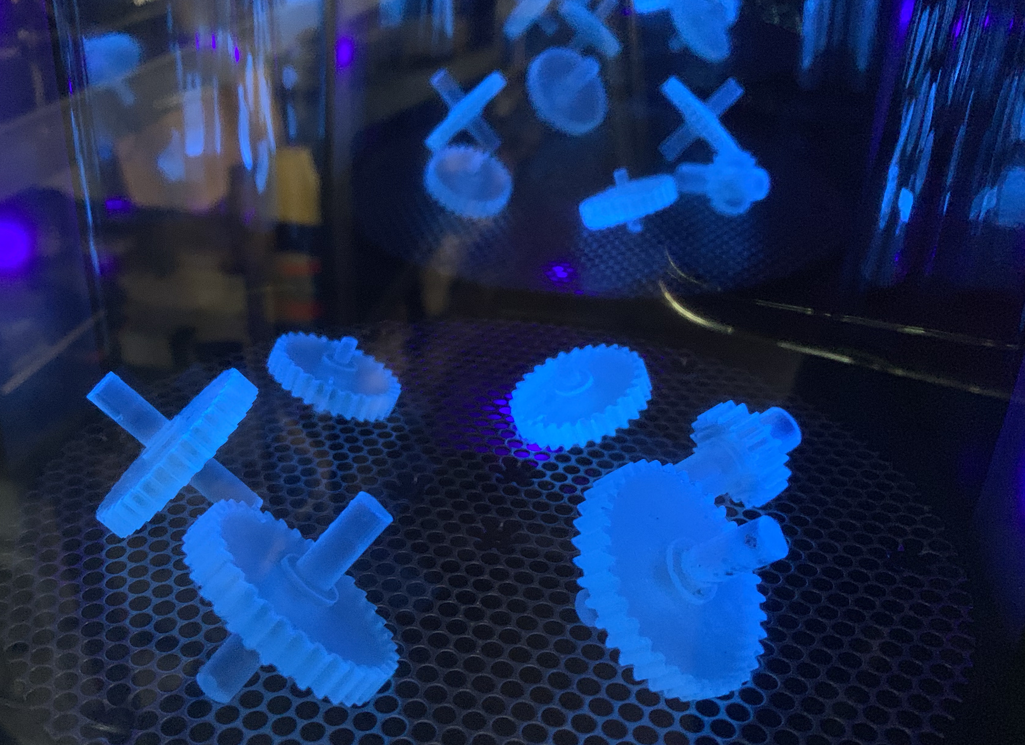 3D printed gears under the glow of 405 nm light in Formlabs Form Cure post-curing chamber.
