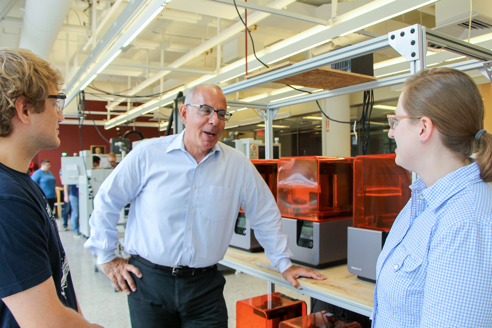 Dr. Fine and Mogenson talk in Boston University's EPIC lab in front of Form 2 3D printers.