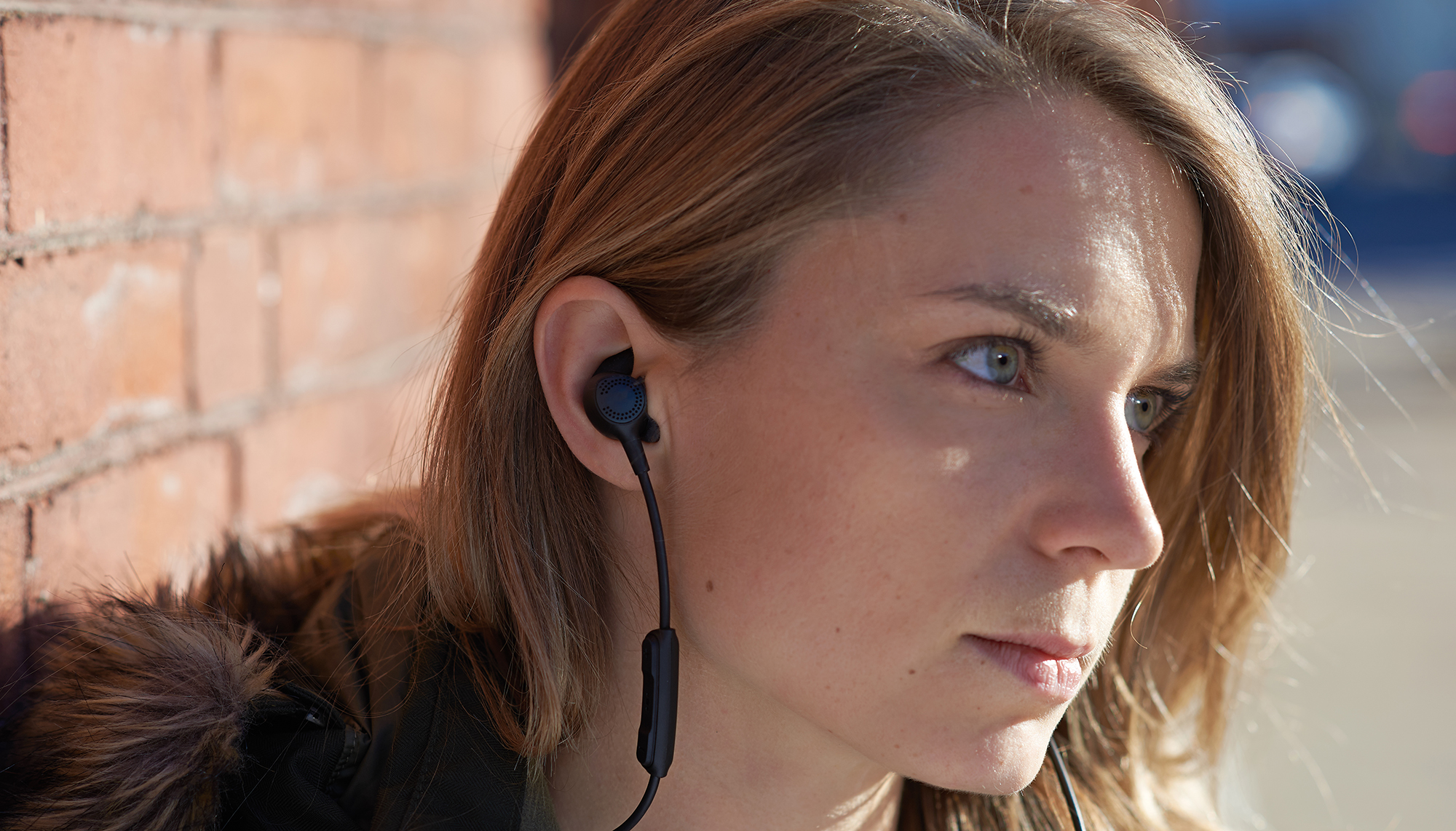 A woman wears earbuds, produced with 3D printing, custom-fit to her inner ear.