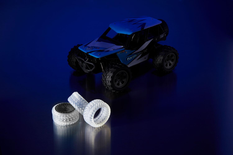 Una macchina radiocomandata (a destra) e dei prototipi di ruote giocattolo (a sinistra) stampati in 3D con l'Elastic Resin.