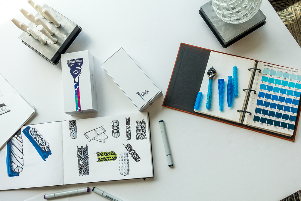 Razor handles designs and printed parts on a designer's desk.