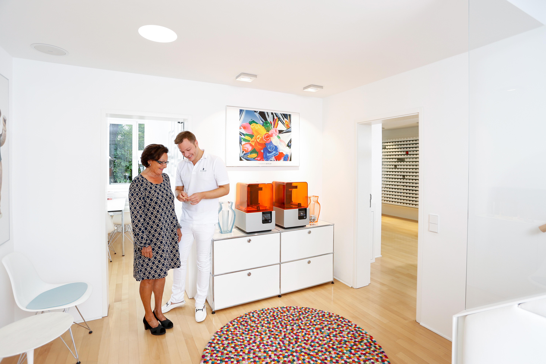 Dr. Sebastian Horvath mit einer Patientin und ihrer 3D-gedruckten Bohrschablone neben den zwei Form 2 3D-Druckern der Gemeinschaftspraxis.