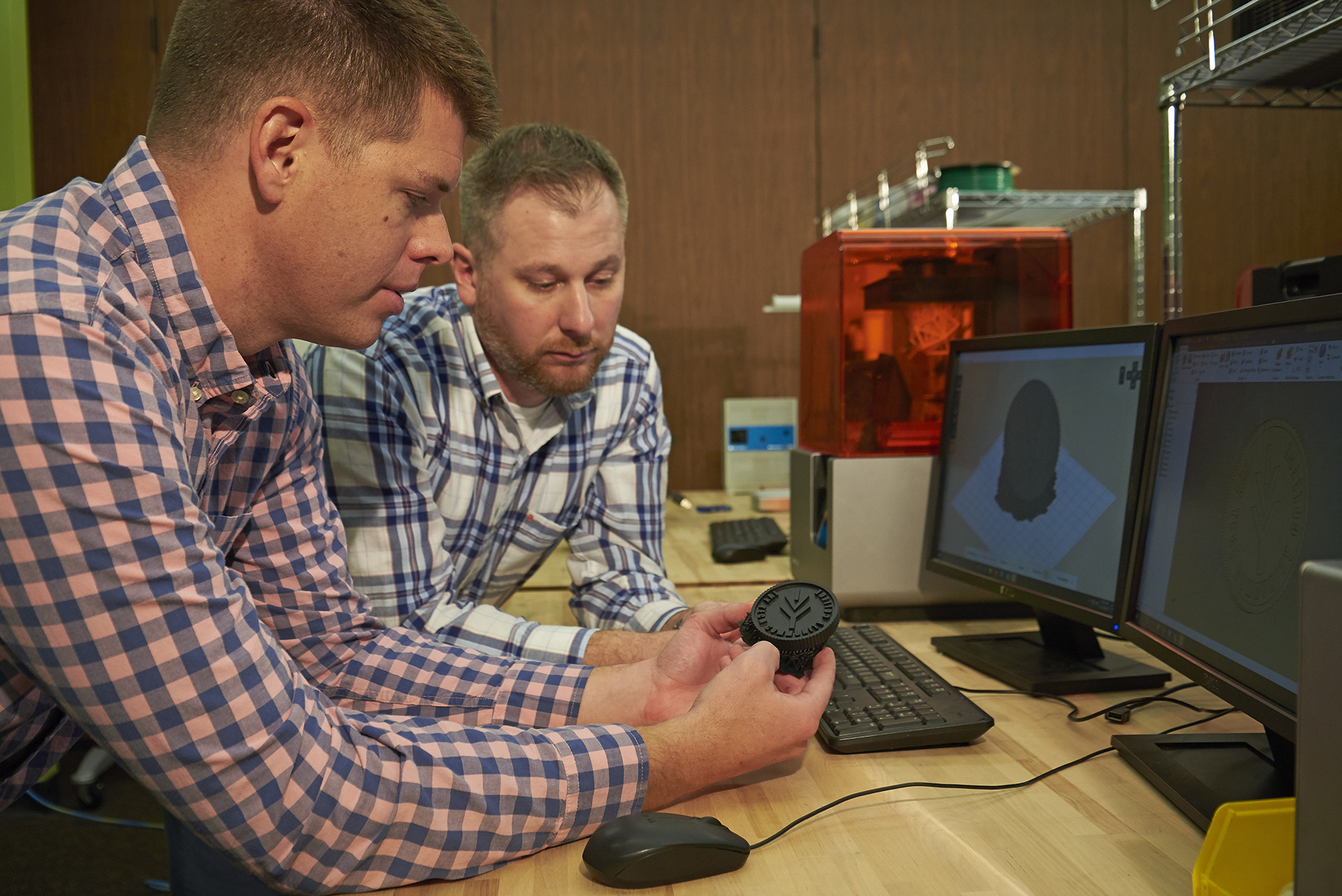 Two professors look at a 3D printed part in front of the Form 2 3D printer.