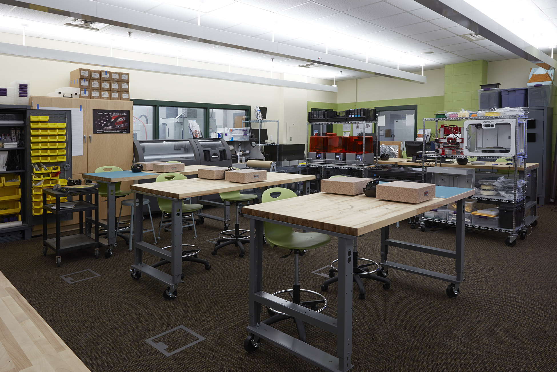 A renovated fab lab that includes moveable benchtops, 3D printers, and supply storage units.