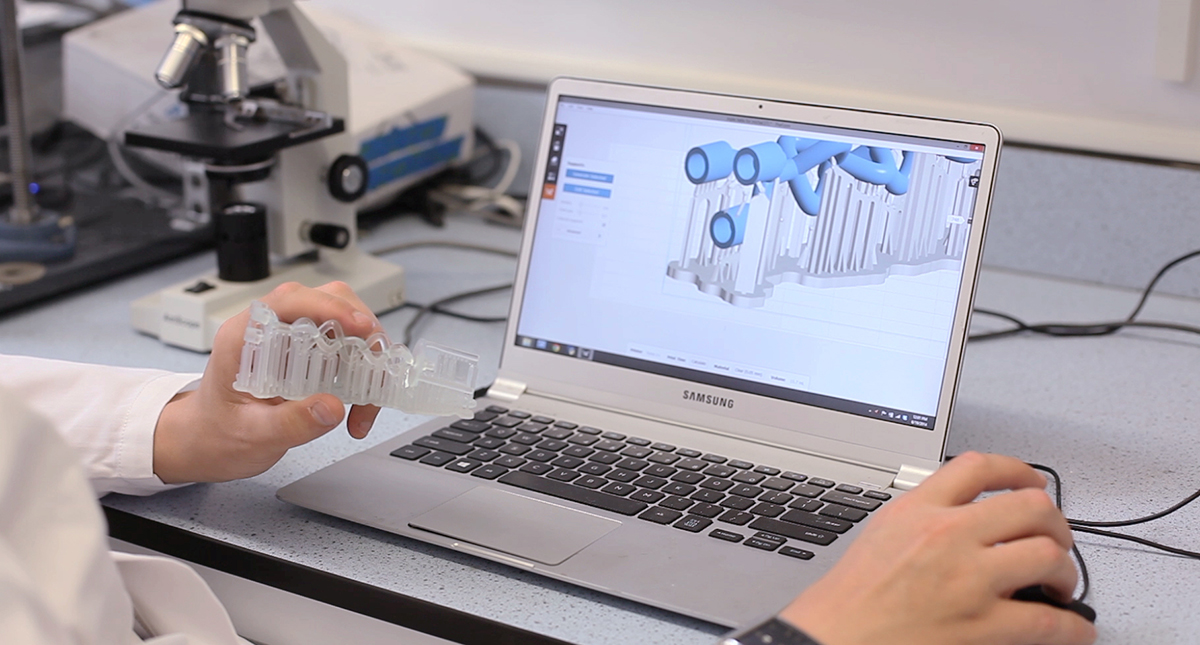 A researcher holds a 3D printed millifluidic device while looking at its design in CAD on a computer. screen