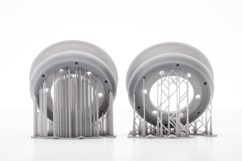 Bei beiden SLA-Systemen werden die Druckteile mit Stützstrukturen an der Konstruktionsplattform befestigt.